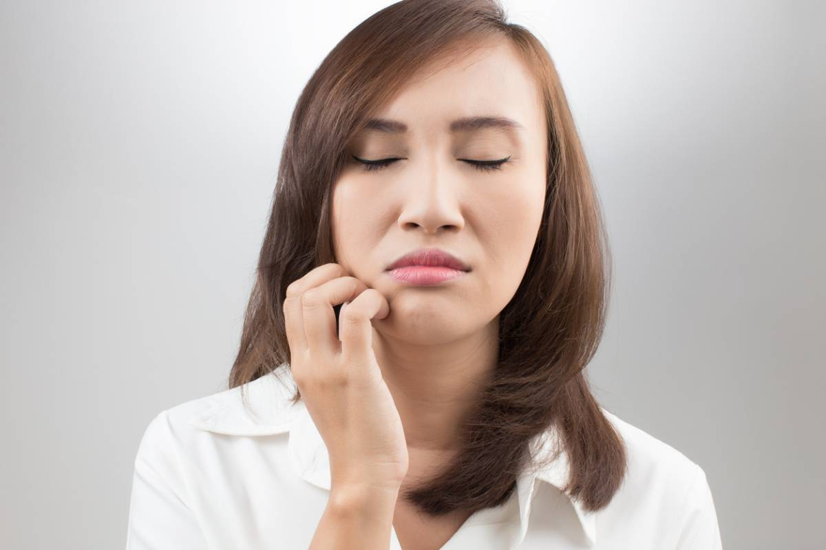Woman scratching at her face that will make acne worse.